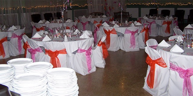 Beautifully decorated tables with pink and red bows.